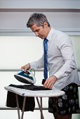 Businessman ironing pants