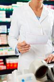 Female Pharmacist in pharmacy, standing at the cashier she is holding a prescription slip in her han