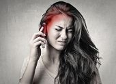 stock photo of noise pollution  - portrait of girl on the phone with headache - JPG