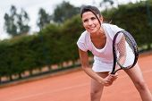 Woman playing tennis at the court and holding racket