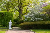stock photo of rockefeller  - A section of a Cleveland city garden with statuary and flowering trees in spring - JPG