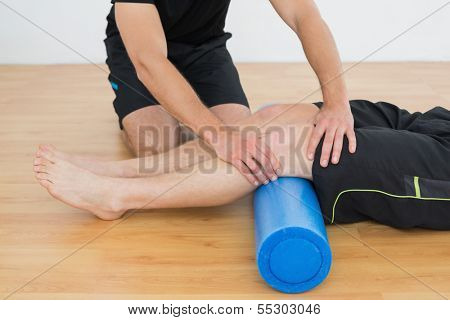Low section of a young man getting his knee examined by a physical therapist