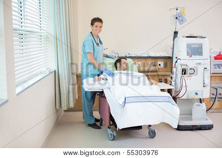 Portrait of female nurse smiling while standing by patient receiving renal dialysis in hospital room
