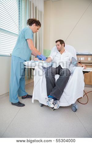 Female nurse setting up dialysis machine on young male patient