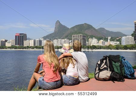 Tourists sitting on the edge of Guanabara Bay watching the Christ the Redeemer.