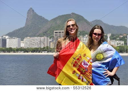 Couple of female sport fans holding the Spanish and Argentinian flag in Rio de Janeiro with Christ the Redeemer in the background.