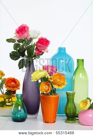 Vases with flowers on a white background