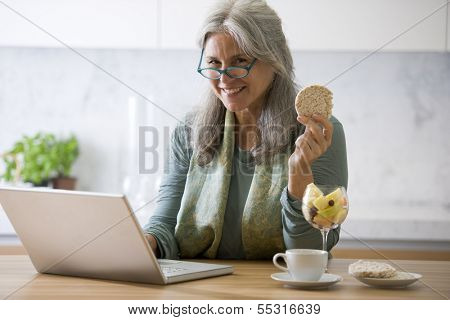 Senior woman working at pc while having breakfast