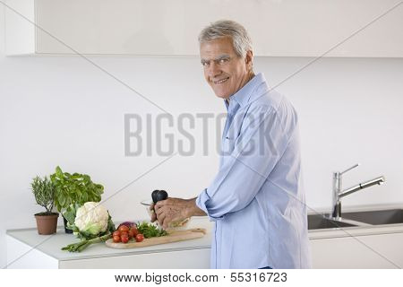 Happy senior man cooking healthy food