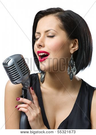 Portrait of female singer with closed eyes wearing black evening dress and keeping microphone, isolated on white. Concept of music and retro fashion