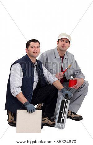 Tile cutter and painter kneeling together