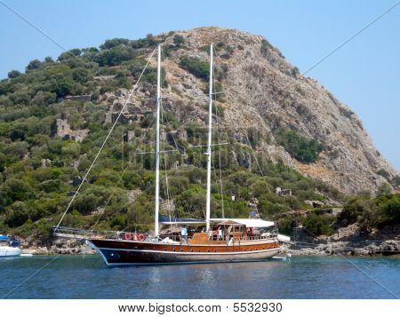 Yacht in front of rock