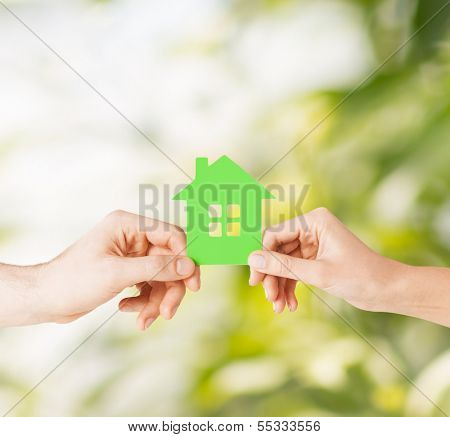 eco, family and real estate concept - closeup picture of woman and man hands holding green house