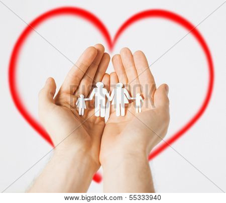 family and happiness concept - man hands showing family of paper men