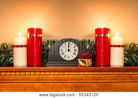 A Christmas mantlepiece with a clock showing midnight and four candles burning bright.