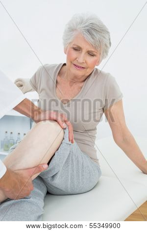 Displeased senior woman getting her leg examined at the medical office