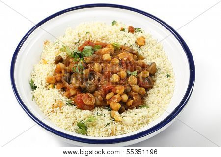 Chickpeas or garbanzo beans and quartered button mushrooms cooked in a spicy tomato and onion sauce and served with couscous mixed with parsley and dried apricots, Moroccan style, served in a tagine