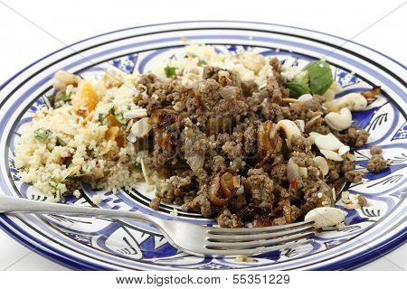 Minced beef cooked with onion and spices, served with couscous and garnished with toasted nuts and caramelised onion in the North African, Moroccan, style
