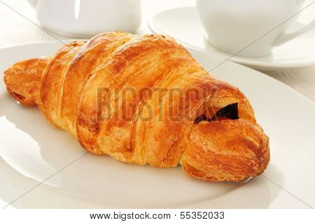 a croissant in a plate on a set table with a cup of coffee in the background