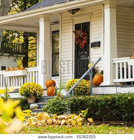 A traditional styled older home decorated in autumn decore.