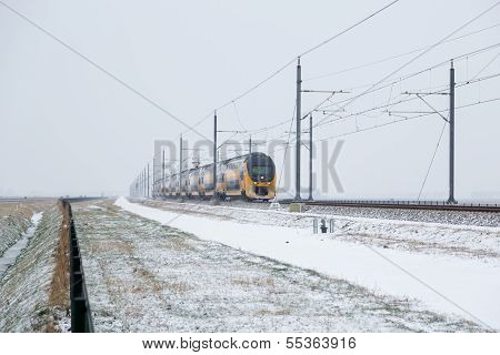 Train In Dutch Rural Winter Landscape During A Snow Shower