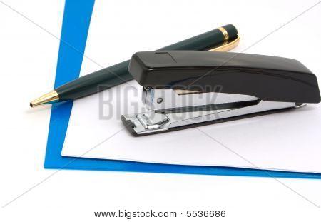 Stapler Pen And Blue Folder On White Background