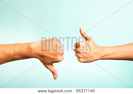 Two hands signalling thumbs up and thumbs down. Hand of man and woman.
