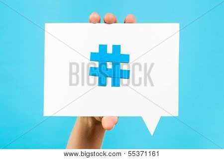 Hand holding a speech bubble with a Hashtag internet notification concept on blue background poster