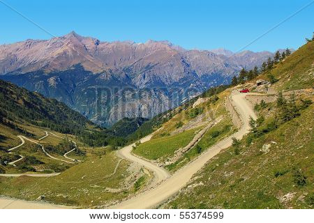 Unpaved road among slopes of hills and mountains in Piedmont, Northern Italy.