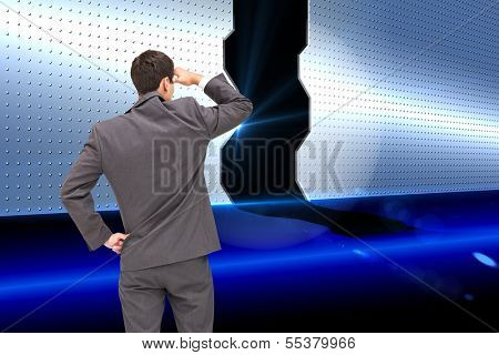 Composite image of businessman standing hand on hip peering