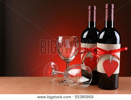 Closeup of a wine bottles decorated for Valentines Day. Two empty wineglasses are next to the bottles with one on its side.  Both bottles have a red ribbon and heart shaped tag and a blank label.