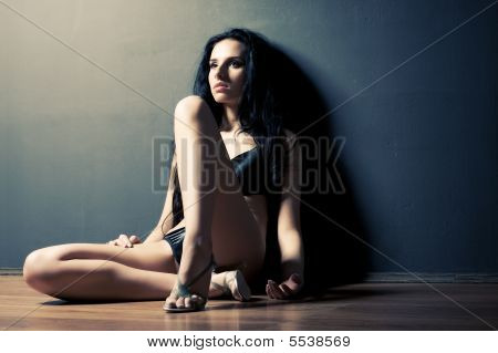 Young Pensive Woman Sitting In A Corner