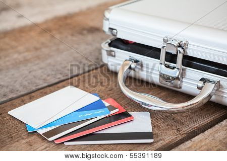 Credit Cards And Opened Steel Case Laying On Wooden Floor