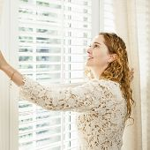 foto of lace-curtain  - Happy woman looking out big bright window with curtains and blinds - JPG