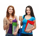 education, technology and people concept - two smiling students with bag, folders, tablet pc and tak