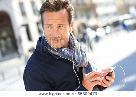 Man in town talking on the phone with handsfree