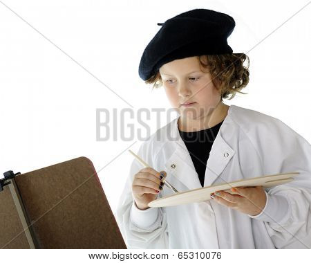 A serious elementary-aged artist wearing a white smock and black beret contemplating her work with paintbrush and palette in hand.  On a white background.