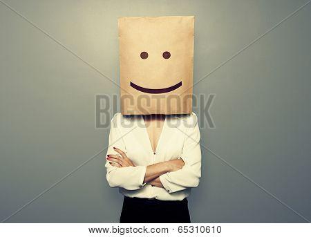 businesswoman hiding under smiley paper bag over dark background