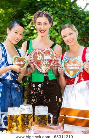 Young women in traditional Bavarian clothes or tracht with a gingerbread souvenir heart in beergarden on Oktoberfest