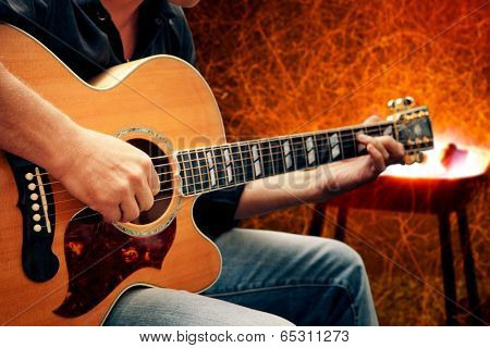 man playing guitar against fire background