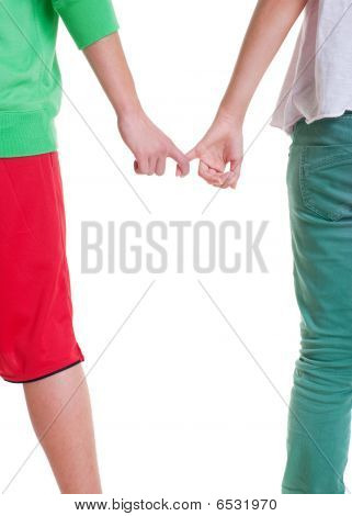 Teenagers Holding Hands Against White Background