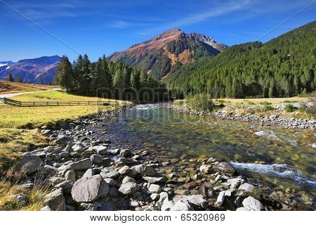 Idyllic landscape. Upper courses of falls - rather narrow fast seething small river among green mountain meadows.  National park Krimml in Austria