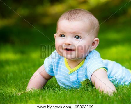 Spring Portrait Of Happy Baby Boy Outdoors On Grass In Field