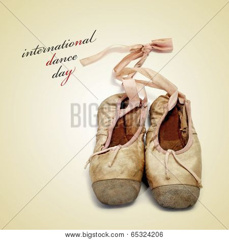 worn pointe shoes and the sentence international dance day on a beige background