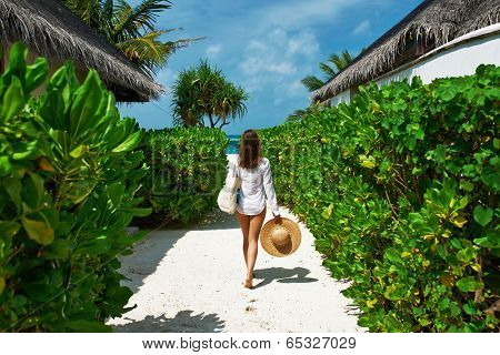 Woman with bag and sun hat going to the beach