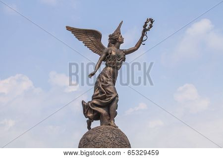 Goddess of victory Nike against the clouds and sky.