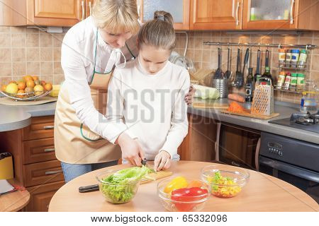 Mother And Daughter Cutting Vegetables For  Salad