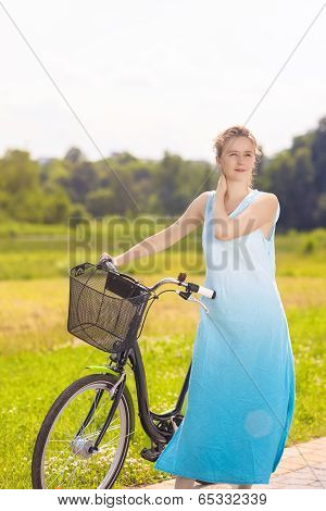 Portrait Of Young Happy Caucasian Blond With Female Bicycle In The Park On A Sunny Day