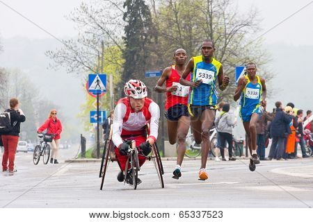 Krakow, Poland - April 28 : Cracovia Marathon.handicapped Man Marathon Runners In A Wheelchair And O