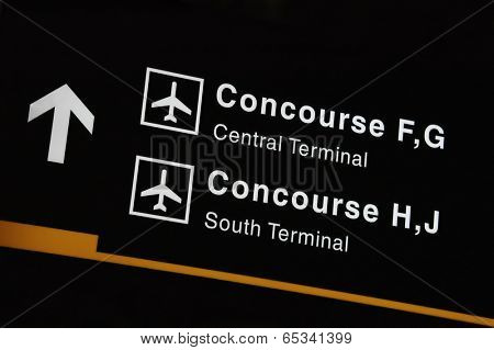 Airport sign showing direction to concourse and terminals